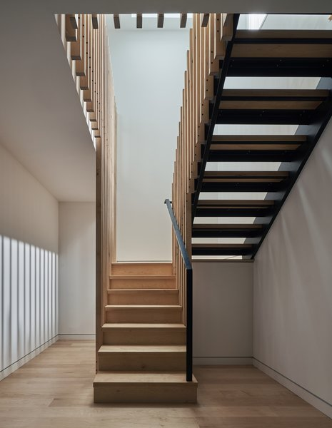 The partial basement holds storage and an entertainment room. A skylight over the stairs floods the area with natural light.