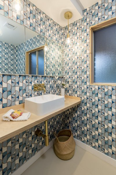 "Wei outfitted the room with Heath Ceramics wallpaper from Hygge & West. ""I'm just generally big into wallpaper and especially in powder rooms,"" says Wei. Blue accents and plywood details are repeated throughout the home to create a consistent throughline."