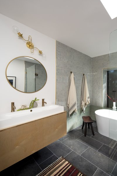 Wei collected the tub and shower in one designated wet area wrapped in tile, then installed a custom vanity.
