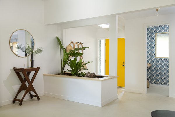 """A raised planter adds character and defines the entryway, while still allowing for connection between the front door and living room. """"You want the space to breathe, but you also want to designate zones,"""" says Wei."""