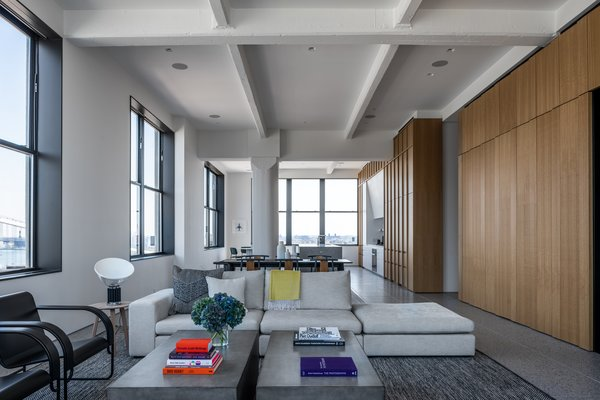 The firm relocated the bedroom and removed the wall in order to cluster all the living areas together. Black-framed windows emphasize the stunning views.