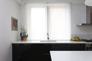 """Preda placed the kitchen sink in front of one of the best views in the apartment. """"The apartment is on the fourth floor, higher than the rooftops of [surrounding] buildings,"""" says Preda. """"So, the sink…aligns with the window that overlooks red clay roofs."""""""