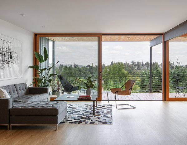 "An expansive glass door trimmed in vertical grain fir opens the interior to the refreshed deck. The designers made sure to keep the frame around the doors thin, in order to capture views and convey the minimal detailing of the original midcentury home. ""All those details that go into keeping that eastern window wall as open and permeable as possible kept the essence of the original house, increased the indoor/outdoor connection, and retained that character that we and the owners had responded to in the house,"" says Griesmeyer."