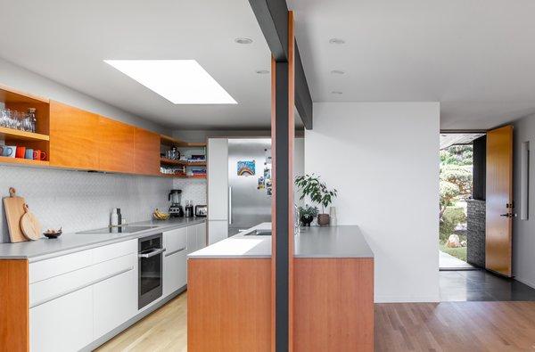 The backsplash tile is Heath Ceramics Dwell Little Diamond in Stone White. A new skylight funnels light into the kitchen.