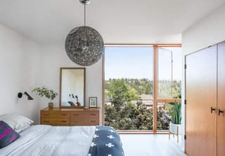 In the master suite, large glass windows convey the view. The dresser is vintage.