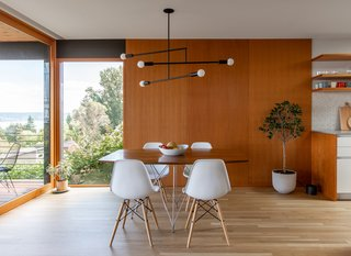 Vertical grain fir panels present a cohesive background for the table, which is surrounded by Eames chairs and illuminated by an Andrew Neyer light.