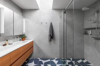 Mutina Puzzle Edge tile is complemented by plaster walls and a fir vanity.