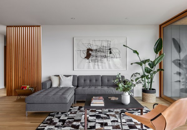 Now, the furniture grouping comfortably occupies the living room. A sectional from Gus Modern sits with a custom steel coffee table and a Paulistano armchair.