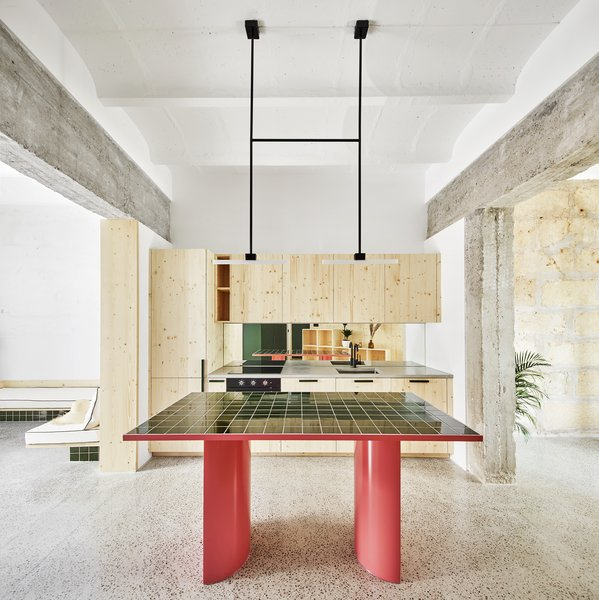 The punchy-colored base of the kitchen work table is a note of contrast against the predominant green accents. The table was custom-designed by Mariana de Delás & 2Monos Studio.