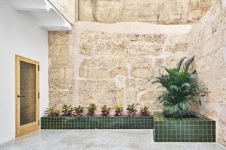 The original limestone walls were cleaned up, and the new design bookends the apartment with courtyard spaces.