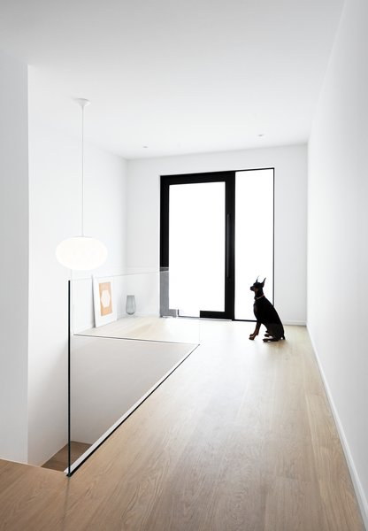 The white backdrop lets the black accents and wood grain in the pale, white-washed flooring stand out. A frameless glass railing melds with the surroundings.