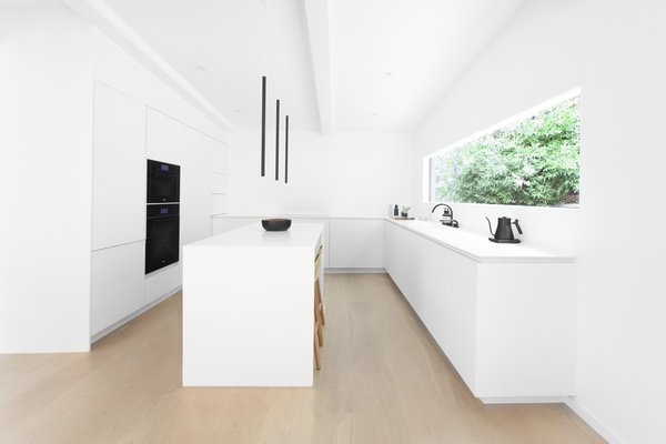 Black wall ovens, streamlined pendants, and a Vola faucet offer notes of contrast in the all-white kitchen. Solid-colored Corian covers the counters and the backsplash. On the window wall, the Corian backsplash is flush with white-painted drywall at the end of the counter run.