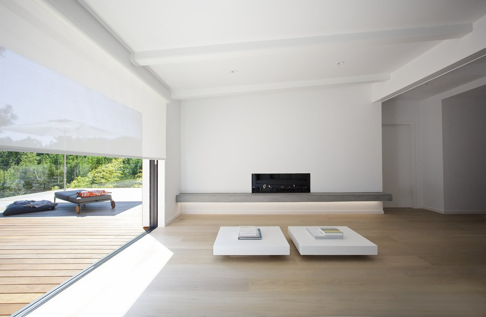Huge header beams and thickened walls allow for a generous opening between the living room and deck, with doors that recess into the wall cavity and a seamless meeting between the indoor floor and the exterior decking.