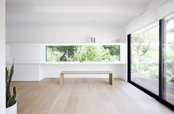 An integrated desk and wall shelf, the latter incorporating hidden LED lighting, frame a ribbon window that appears frameless to better merge with the treetop view.