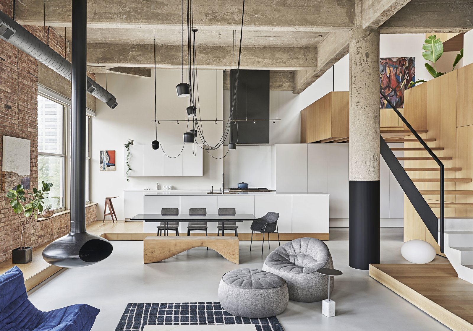 The wood through-line continues throughout the main space with a raised platform that wraps the perimeter of the room. The platform surrounds the living and dining area, and runs beneath the sleeping zone and stair landing.