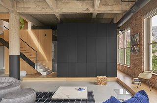 "The master bedroom, or ""sleeping cube,"" is tucked inside a black steel framework with a storage side facing the living room."