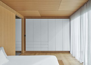 The walls are thickened by closet storage on two sides, which also controls the interior temperature and dampens sound.