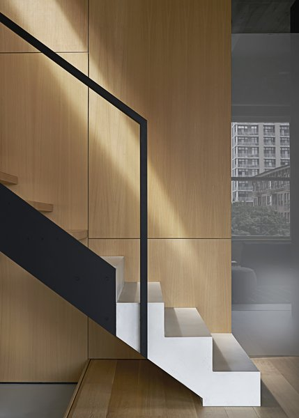 The staircase is a sculptural feature that brings together all of the elements of the project palette, including white concrete at the base, wood, and black steel. The white concrete is meant to appear as though it is emerging from the wood platform.