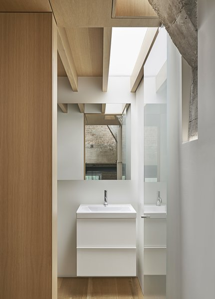 """The bathroom skylight was a discovery made during construction. The contractor hadn't yet finished the floor above, says Radutny: """"One of the joists had an opening and it just looked like that wanted to stay open. So that became an opportunity to borrow more light into that room and create a visual connection."""""""
