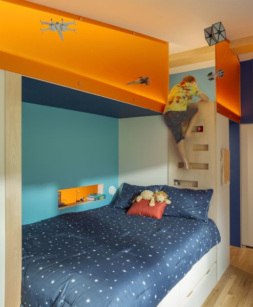 This room had multiple constraints: three walls had doors that could not be moved, and the remaining wall had a ceiling height that could not accommodate a loft bed. The solution was to build the custom bed, ladder, loft, and shelving unit in the middle of the room where the ceiling is peaked.