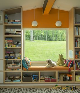 Now, the playroom can be accessed by the son's bedroom or at the hallway. Custom woodwork fashions storage and a window seat.