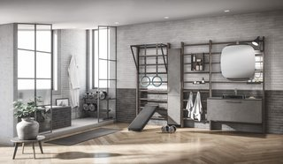 Here, Gym Space is combined with Scavolini's Aquo bathroom line. The dark wood wall bars (in the Core colorway) are fitted with various equipment—such as a lamp and containers in a matte Anthracite finish. Additional exercise accessories include an eco-leather bench and a matte black structure and traction bar.