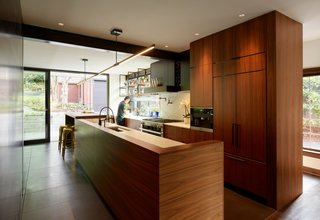 "The expansive new kitchen has a generous sliding glass door to the yard and cabinetry is outfitted in plain-sawn walnut. ""The wood is close in tone to the existing mahogany woodwork, but it has a more expressive grain,"" says Chadbourne. ""We used it at all new cabinetry in flat, flush panels. The walnut's grain character is the design element rather than the cabinetry construction details."""