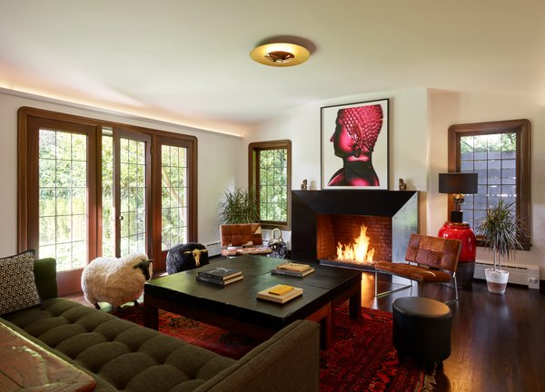 "In the living room, a new faceted, blackened-steel fireplace surround is juxtaposed with leaded glass windows. ""The existing portions of the house offer more formal and internal spaces for cozy entertaining and lounging,"" says Chadbourne."