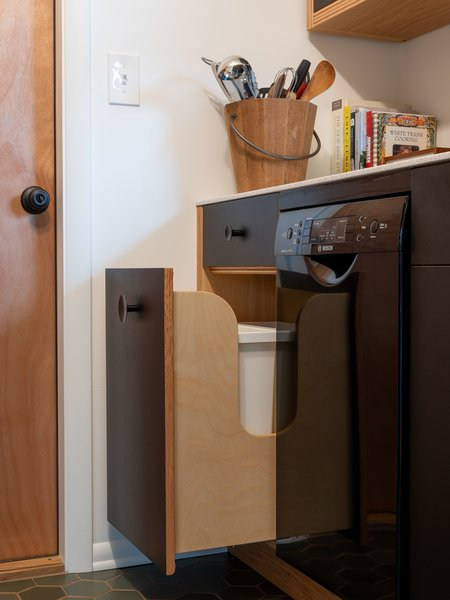A black, 18-inch Bosch dishwasher and black hardware from Schoolhouse Electric disappear against the cabinet fronts, rather than cluttering the small room with distracting detail.