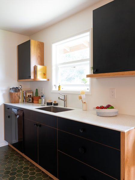 """The kitchen flooring is dark green, seconds tile from local tile maker Pratt & Larson—purportedly rejects from the Starbucks coffee chain. The tan-colored grout is """"copacetic"""" with the wood floors."""