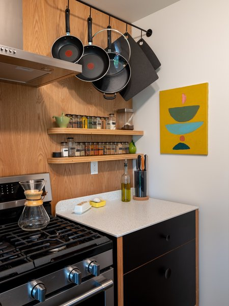 Ben fashioned the stove-side cabinet as a freestanding unit. This area functions as the couple's main prep space, and a deep drawer below holds bigger appliances like the food processor and a stock pot. The custom pot rack is by Kari Merkl of the local design and manufacturing company Merkled Studio.