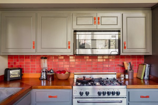 Bailey integrated red and yellow accents throughout the cabin in a nod to its '70s origins. Paprika-colored Heath tile bedecks the backsplash. The matte-black, enamel cast iron pan is by Crane Cookware.