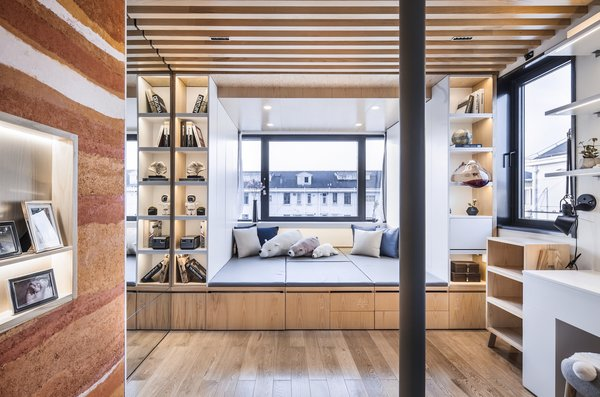 A view of the master bedroom portion of the apartment illustrates how the designers made every square inch of the home multifunctional. The bed platform is surrounded by smart storage, including various drawers, and doubles as a stage for singing or extra seating on movie nights.
