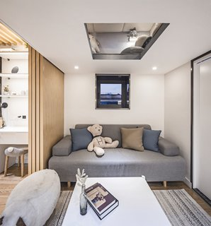 Now, a folding wood wall separates the living room from the master bedroom area. The designers also created a mezzanine above the living room that hosts the daughter's playroom and can be accessed by a rolling ladder. The door to the right leads to the new bathroom.