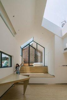 Occupants on the roof terrace can look down into the addition via the skylight. A narrow window over the table affords a view of the street, and the built-in table's triangular shape saves space.