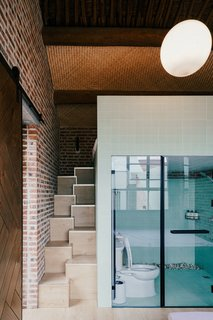 Green tile covers the bathroom for consistency with the exterior. The steps lead up to a loft above the bathroom cube.