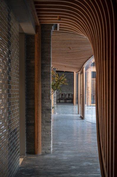 Curvilinear wood slats form the interior ceiling of the inserted veranda. A tile wall mimics the original restored brick.