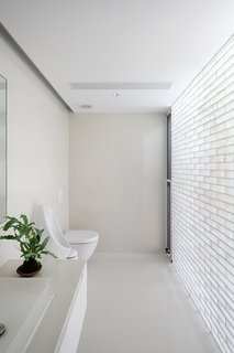 The color palette was reversed in the bathroom—glass brick lines the wall in a nod to the other materials in the project.