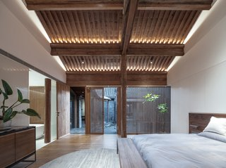 The bedrooms can also open to the back courtyard. Wood floors are a warmer material in the bedroom and sync with the restored wood on the ceiling.
