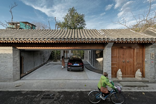 """The restored facade of the Quishe Courtyard by ARCHSTUDIO references the melding of traditional and modern architecture within. """"Qi"""" means """"seven"""" in Mandarin, and """"she"""" means """"house,"""" giving the project its name; its address in the hutong is seven, and it originally boasted seven pitched-roof buildings."""