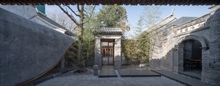 The entry gate now functions as the front door to the residence. The front courtyard doubles as the garage. On the left, the gray roof of the veranda flows downward to obscure the functional spaces behind it, including wash rooms and a service room.