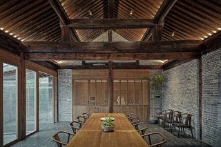 A dining room bisects the property and sits between the middle and rear courtyards. It has an adjacent kitchen tucked off to the side.
