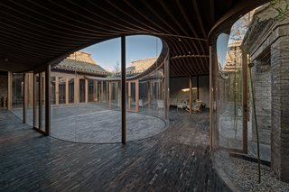 A derelict courtyard residence gets revitalized with a sinuous, glass-walled pathway.