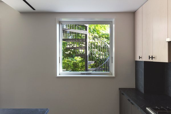 """""""In the existing original condition, the upper unit had to come through the interior of the lower unit to get outside,"""" says Thomas. The addition of an exterior spiral staircase and outdoor terrace now connects the sister's upstairs kitchen to the yard below. A new window frames the view of the staircase."""