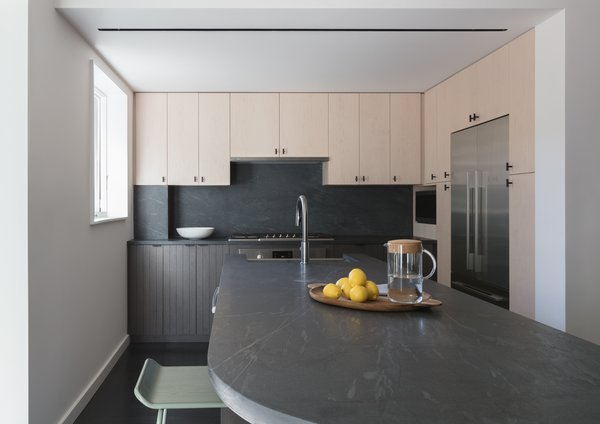In the kitchen, the countertops and backsplash are Pietra Cardosa stone and the cabinetry is whitened maple and an ebony-stained charcoal oak, to sync with the rest of the case goods throughout the home.