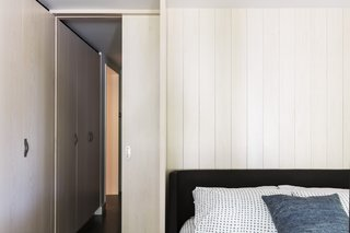 Sleek whitened-maple storage lines the threshold between the master bedroom and the nest room. A pocket door separates them.