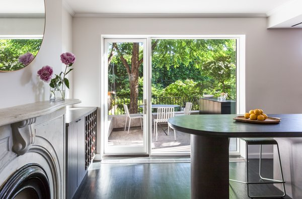An elongated kitchen island is a spot to eat, and protects the cook from foot traffic. A large picture window and glass door connects the new outdoor terrace to the interior spaces.