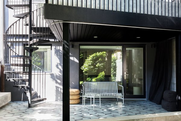 """The spiral staircase connects both units to the backyard space. """"The vertical stair provides an efficient path for her two young nephews to slip directly down from their kitchen to the back yard to play or for group barbecues with the extended family,"""" says the firm."""