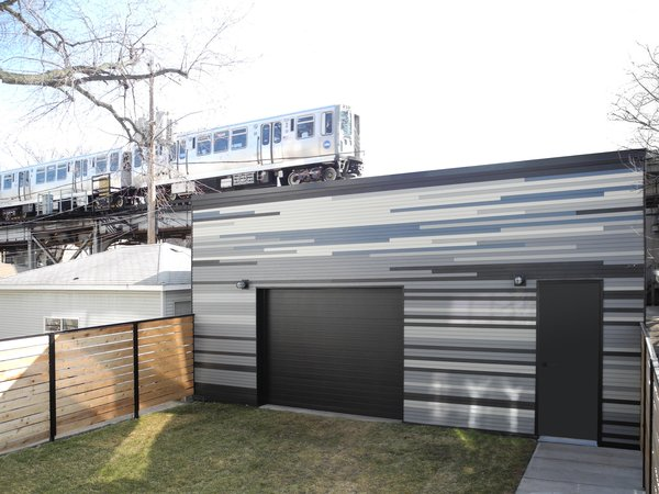 """At the garage, """"the material is the same cladding as the addition and the back of the house— Hardie Boards were applied in a totally random pattern, with the intent to paint the surface,"""" says Radutny. """"When it was done, I was pleasantly surprised with the accidental outcome and suggested for it to be left as is. The result was rather beautiful, echoing a sense of movement as the foreground to the Elevated Train above. So, they left it, as another art wall."""""""