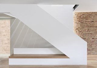 """At the entry, the staircase takes on a sculptural quality and integrates a built-in bench. On the right, the home's preserved brick is revealed. On the left, a window captures the exterior brick of a neighbor. """"We created these moments where the inside and the outside start to blend together,"""" says Radutny."""